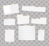 Ripped white ruled note, notebook, copybook paper sheets stuck with yellow sticky tape on pattern created of heart Royalty Free Stock Photo