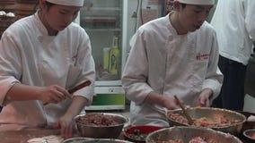 Rippenstückchefs, die dim sum-Mehlkloßlebensmittel an touristischem Handelszentrum Yuyuan in Shanghai, China zubereiten stock video footage