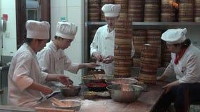Rippenstückchefs, die dim sum-Mehlkloßlebensmittel an touristischem Handelszentrum Yuyuan in Shanghai, China zubereiten stock footage