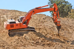 Ripper. Large track hoe excavator using a claw ripper to break up rock and soil for fill for a new commercial development road construction project Royalty Free Stock Photography