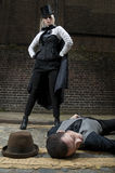 Ripper and victim. Woman dressed as Jack the Ripper on top of man lying on the ground Stock Image