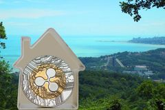 Ripple coin in a metal house. On a sea cost background. Rent or buy a house for XRP Stock Photo