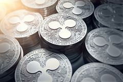 Ripple coins XRP in blurry closeup with sun flare. New cryptocurrency and modern banking concept. 3D rendering stock illustration