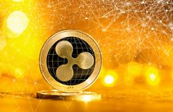Ripple cryptocurrency coin. On a bright gold background Stock Photo
