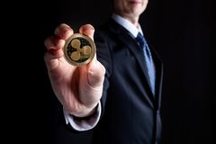 Ripple cryptocurrency coin held with a man in a suit Stock Photo