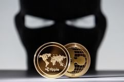 Free Ripple Golden Coins With A Robber Hacker Wearing Face Mask Royalty Free Stock Photo - 118721145