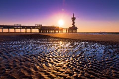 Ripple pier silhouette. Evening silhouette of the pier of Scheveningen, the Netherlands, with ripples in the sand with water on the beach Stock Image