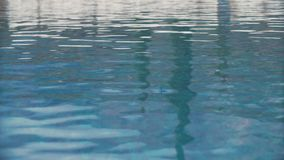 Ripple water surface of swimming pool with blue tiled bottom stock video