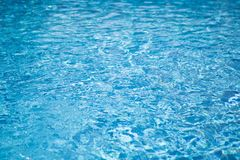 Ripple water in swimming pool with sun reflection. Blue water abstract background.  royalty free stock images