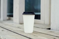 Ripple white paper cup of coffee to takeaway at the wooden floor terrace outside. Ripple white paper cup of coffee to takeaway at the wooden floor terrace Stock Photos