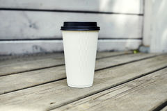 Ripple white paper cup of coffee to takeaway at the wooden floor terrace outside. Ripple white paper cup of coffee to takeaway at the wooden floor terrace Royalty Free Stock Image