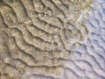 Rippled sandy bottom of the river with flecks of sunlight. Rippled bottom of the river royalty free stock images