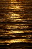 Rippled ocean surface glows with rich copper color at sundown
