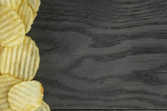Rippled organic chips border on wooden table Royalty Free Stock Photos