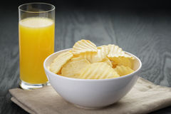 Rippled organic chips in white bowl with orange Royalty Free Stock Image