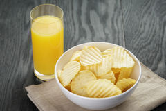 Rippled organic chips in white bowl with orange Royalty Free Stock Images