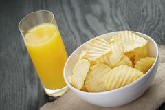 Rippled organic chips in white bowl with orange Stock Image