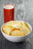 Rippled organic chips in white bowl wit tomato Royalty Free Stock Photography