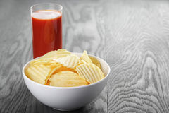 Rippled organic chips in white bowl wit tomato Stock Images