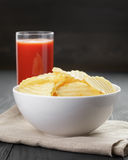 Rippled organic chips in white bowl wit tomato Royalty Free Stock Photo