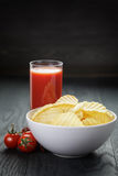 Rippled organic chips in white bowl wit tomato Stock Photo