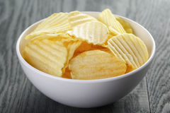 Rippled organic chips in white bowl on wooden Stock Images