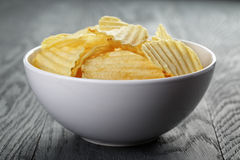 Rippled organic chips in white bowl on wooden Royalty Free Stock Photo