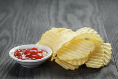 Rippled organic chips wit tomato sauce on wooden Stock Images