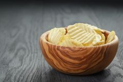 Rippled organic chips in wood bowl on wooden table Royalty Free Stock Photo