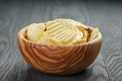 Rippled organic chips in wood bowl on wooden table Royalty Free Stock Image