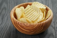 Rippled organic chips in wood bowl on wooden table Stock Images
