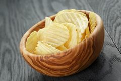 Rippled organic chips in wood bowl on wooden table Royalty Free Stock Images