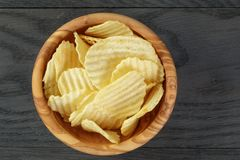 Rippled organic chips in wood bowl on wooden table Royalty Free Stock Photos