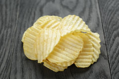 Rippled organic chips on wooden table Stock Photo