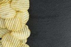 Rippled organic potasto chips on slate board Stock Images