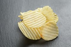 Rippled organic potasto chips on slate board Stock Photo