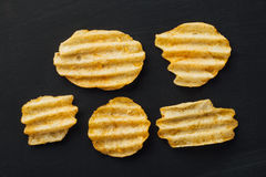 Rippled potato chips on black Royalty Free Stock Photos