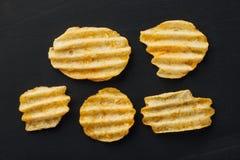 Rippled potato chips on black Royalty Free Stock Photos