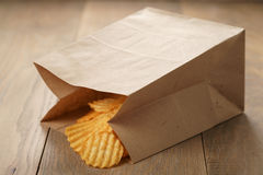 Rippled potato chips with paprika in paper bag Stock Photography