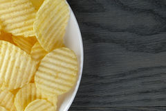 Rippled potato chips in white plate on wood table Stock Images