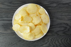 Rippled potato chips in white plate on wood table Stock Image