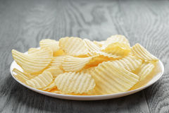 Rippled potato chips in white plate on wood table Stock Photography
