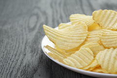 Rippled potato chips in white plate on wood table Royalty Free Stock Photo