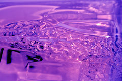 Rippled Purple Glass. An extreme closeup of rippled purple glass bottle Royalty Free Stock Photography