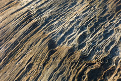 Rippled rock beside the sea background. Royalty Free Stock Photography