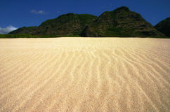 Rippled Sand Landscape. Landscape shot of rippled sand reaching toward green mountains with blue sky behind.  Taken at beach in Hawaii Royalty Free Stock Image