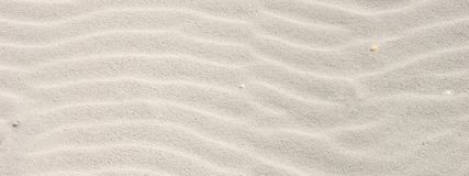 Rippled sand on the sea coast formed by wind and water, background. Texture, pattern, banner stock photo