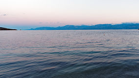 Rippled Sea Water at Dawn. Gently rippled and textured sea water at dawn, in a Corinthian Gulf bay, with views across to blue Peloponnese mountains, Greece Royalty Free Stock Image