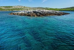 Crystal clear sea water and rocky islet with coastline in the background. Rippled surface of clear and transparent sea water and rocky islet royalty free stock photography