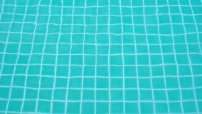 Rippled surface of swimming pool blue water sun reflecting